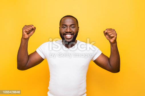 1092211952 istock photo Portrait of cheerful excited delighted mulato man, showing winning gesture, celebrating, isolated over bright vivid yellow background 1055426646