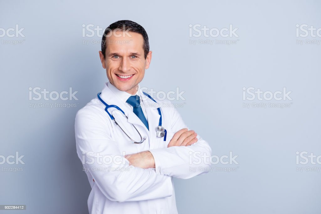 Portrait of cheerful experienced glad professional confident relaxed smart qualified with shiny toothy smile doctor standing with crossed hands blue tie isolated on gray background copy-space stock photo