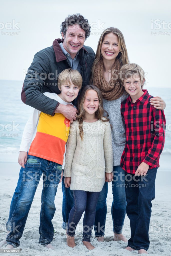 Portrait of cheerful family standing at sea shore stock photo