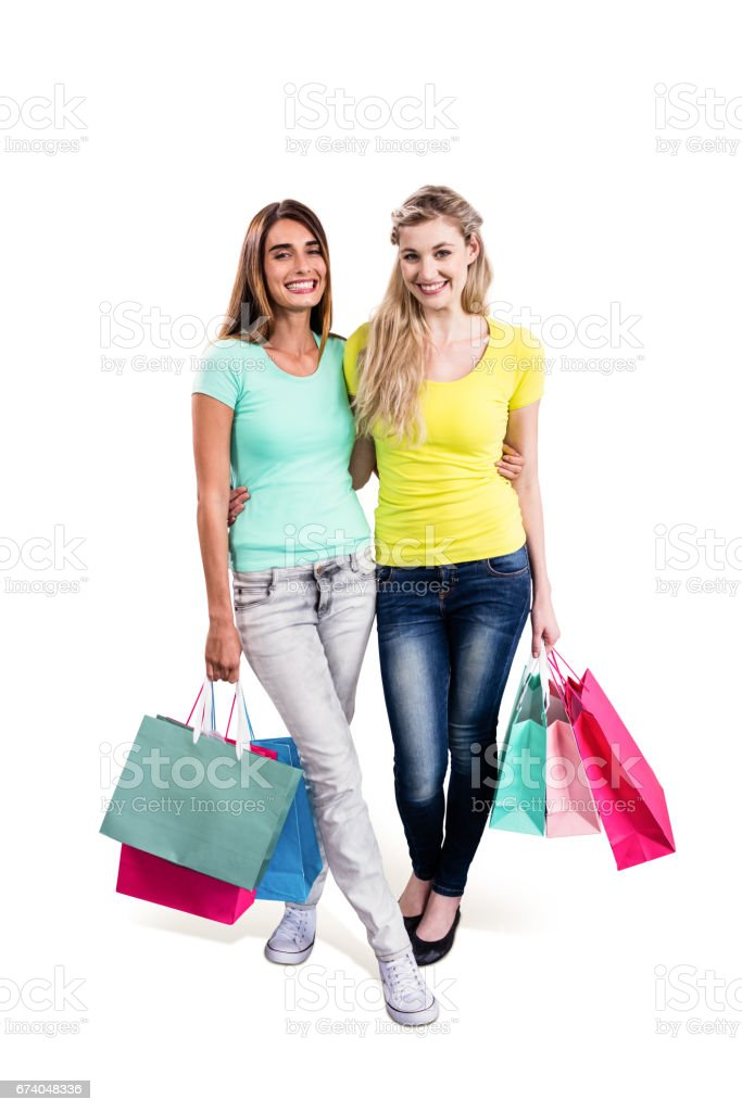 Portrait of cheerful female friends holding shopping bags royalty-free stock photo