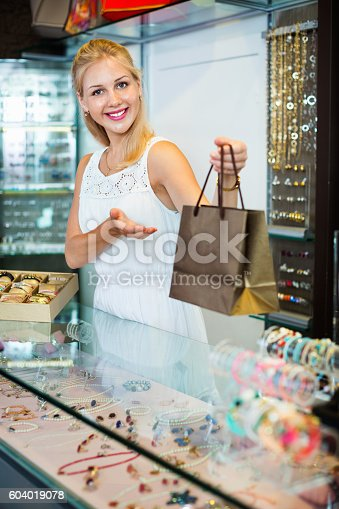 istock Portrait of cheerful female jeweller with glass showcases 604019078