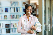 A cheerful mature female librarian stands in her library and smiles for the camera.  She holds a stack of books as she laughs.