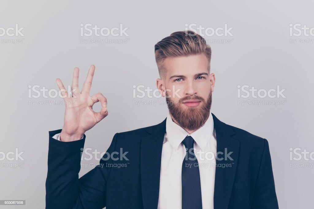 Portrait of cheerful focused satisfied delightful experienced qualified handsome brutal macho with modern haircut tie white shirt demonstrating ok symbol isolated on gray background stock photo