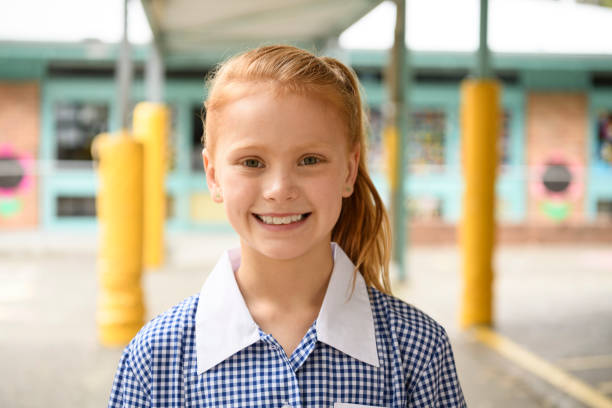 Portrait of cheerful girl with red hair smiling towards camera Girl in school uniform and pony tail looking forward with smile on face 8 9 years stock pictures, royalty-free photos & images