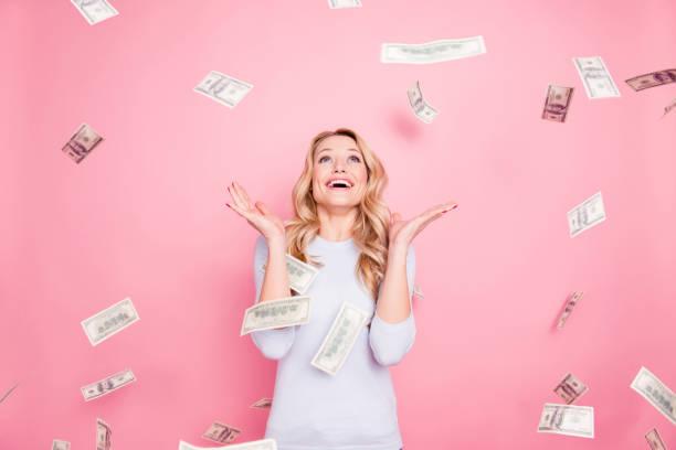 porträt von fröhlichen froh mädchen genießen dusche von 100 hundert dollar, geld, gestikulieren mit den händen fliegen auf rosa hintergrund isoliert - erfolgreich wünschen stock-fotos und bilder