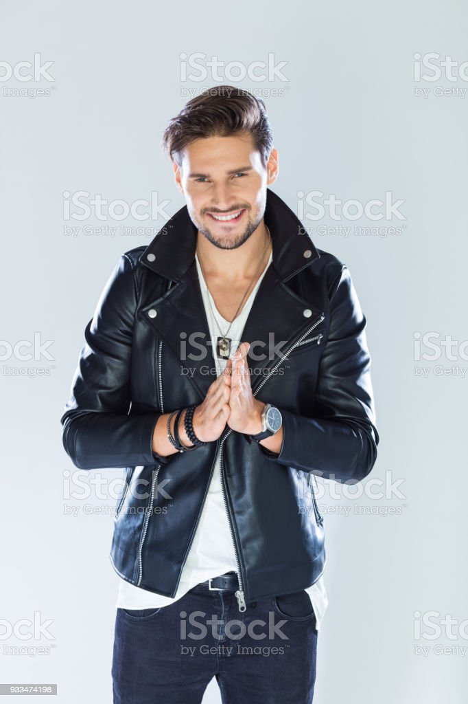 Portrait of cheerful, handsome man wearing leather jacket Fashion portrait of handsome man wearing black leather jacket, smiling at camera. Studio shot, grey background. 25-29 Years Stock Photo