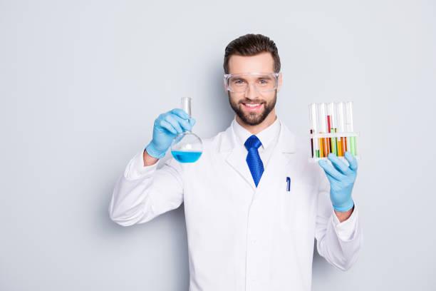 灰色の背景の上のカメラを見て白衣、ネクタイ、試験管とマルチカラーの液体でフラスコを持つ保護メガネで剛毛で陽気なハンサムな科学者の肖像 ストックフォト