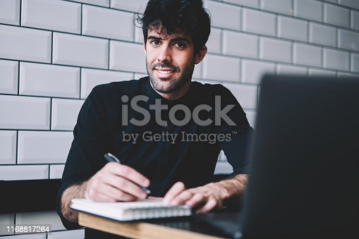 Portrait of cheerful handsome student smiling at camera while wrting down notes in notebook during e-learning at laptop computer in coworking.Positive young man noting records in notepad