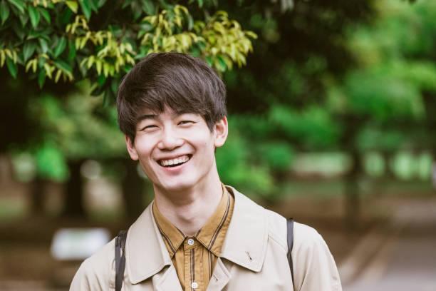 笑顔の陽気な日本の青年の肖像 - 男性のみ ストックフォトと画像