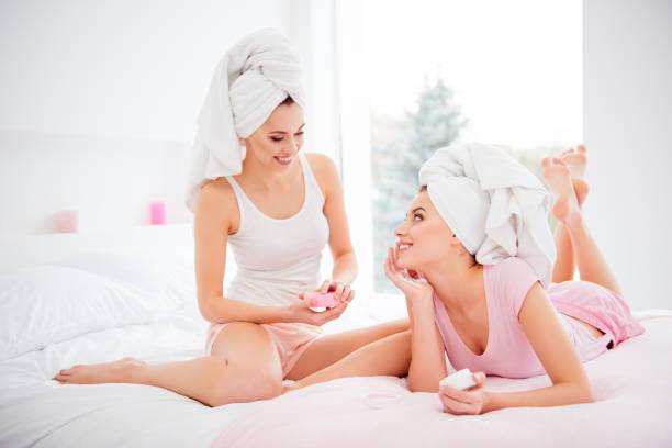 Retrato de la alegre, alegre, encantador, atractivo, bonito, limpio, claro, puras chicas lavaron cabello con toalla en la cabeza, sentado, acostado en cama, uso bálsamo cara para seco, suave suave y engrasado piel - foto de stock
