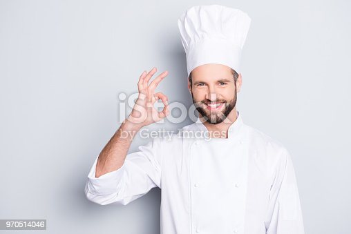 istock Portrait of cheerful joyful chef cook in beret and white outfit with stubble looking at camera showing ok sign, approve, advice menu isolated on grey background 970514046