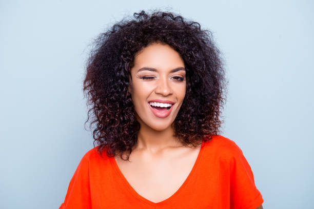 portrait of cheerful joyful woman in orange outfit with modern hairdo winking with one eye looking at camera isolated on grey background. affection dream feelings concept - blinking stock pictures, royalty-free photos & images