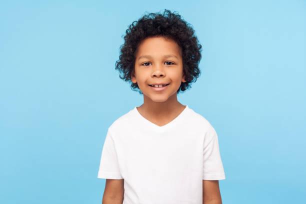 porträtt av glad liten pojke med lockigt hår i t-shirt leende rolig och sorglös, visar två framtänder, friska glada barn - 6 7 år bildbanksfoton och bilder