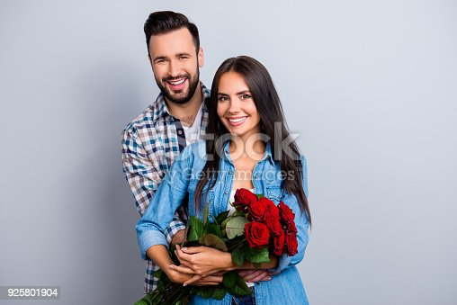 istock Portrait of cheerful lovely cute couple with beaming smiles hugging and looking at camera, woman hold a bouquet of red roses on 14 february, celebrating anniversary over grey background 925801904