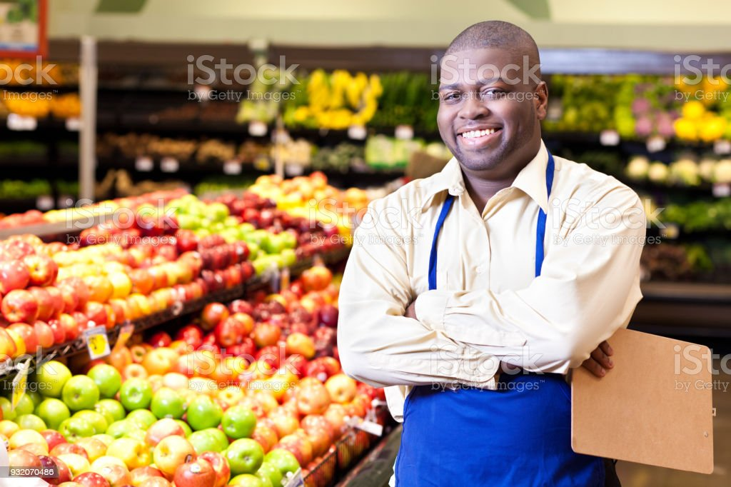 Portrait of cheerful male grocer standing in produce section stock photo
