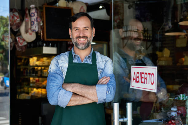 Portrait of Cheerful Male Shopkeeper Standing at Front Door stock photo