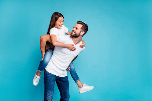 Portrait of cheerful man holding his kid with brunette hairstyle piggyback wearing white t-shirt denim jeans isolated over blue background