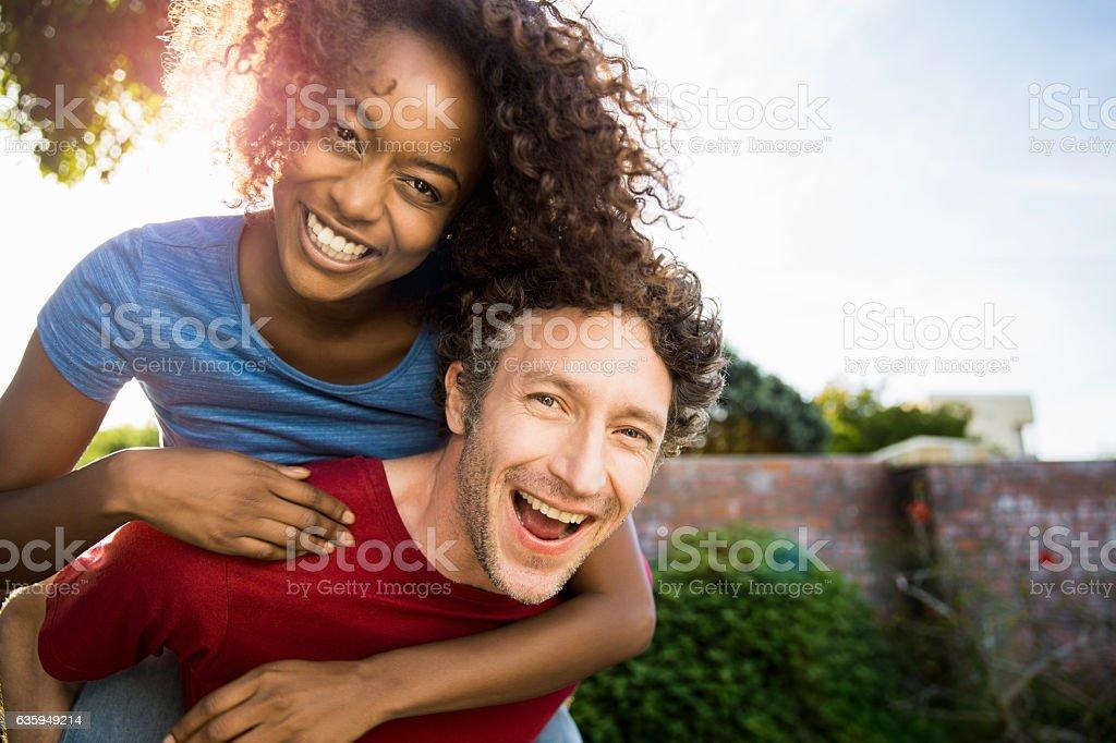 Portrait of cheerful man piggybacking woman – Foto
