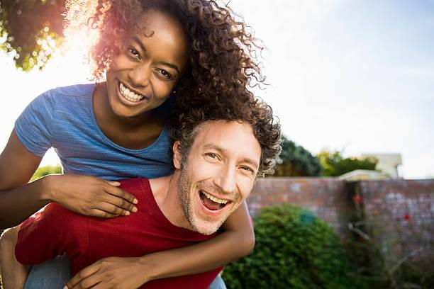 Portrait of cheerful man piggybacking woman stock photo