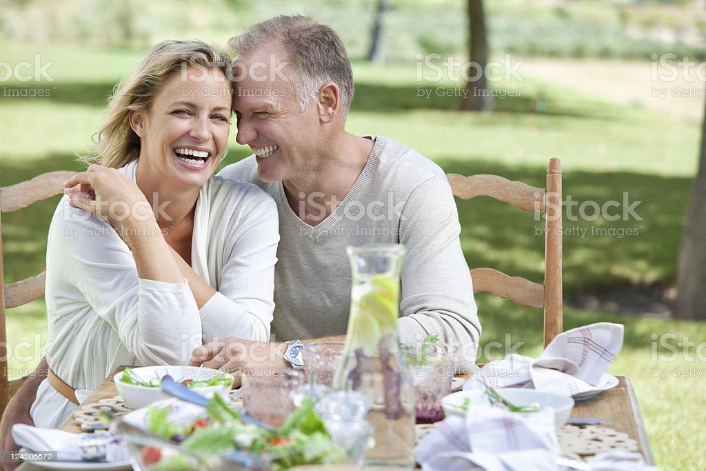 Portrait of cheerful mature couple enjoying breakfast in lawn royalty-free stock photo