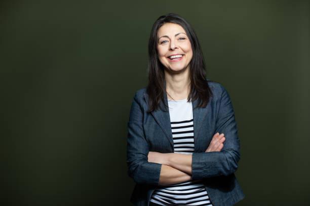 Portrait of cheerful mature woman on dark background stock photo
