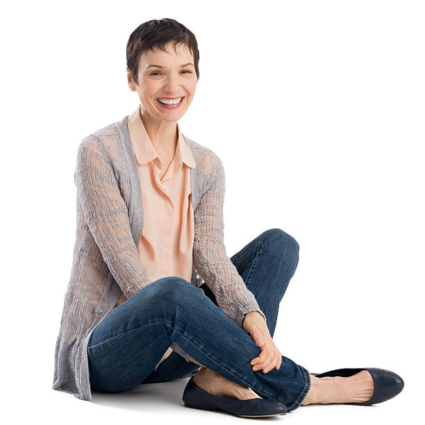 portrait of cheerful mature woman sitting - sitting on floor stock photos and pictures