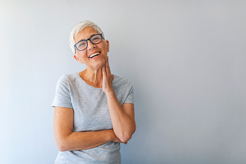 Close up portrait of a professional business woman smiling. Portrait of cheerful mature woman standing against grey wall. Close up portrait of beautiful older woman smiling and standing by wall