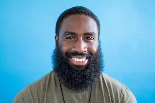 Front view close-up of 31 year old black man with short hair and full beard wearing gray t-shirt and smiling at camera against blue background.