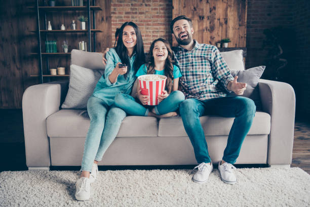 portrait of cheerful mom dad and little kid have rest laugh look funny film wear denim jeans checkered shirt t-shirt sit divan in house indoors - watch imagens e fotografias de stock