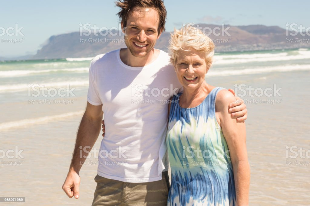 Portrait of cheerful mother and son standing on shore foto de stock royalty-free