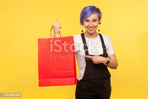 Portrait of cheerful nice hipster girl with violet short hair in denim overalls pointing at shopping bags, showing packages, discounts and sales in store. isolated on yellow background, studio shot