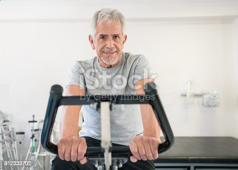 istock Portrait of cheerful old man at physiotherapy looking at camera smiling 912333702