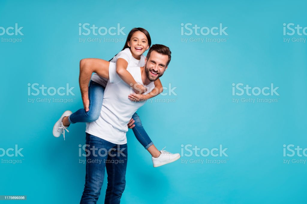 Portrait of cheerful people laughing piggyback wearing white t-shirt denim jeans isolated over blue background Portrait of cheerful people laughing piggyback wearing white t-shirt denim, jeans isolated over blue background Adult Stock Photo