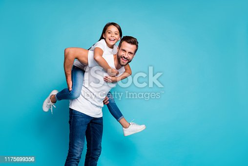 Portrait of cheerful people laughing piggyback wearing white t-shirt denim, jeans isolated over blue background