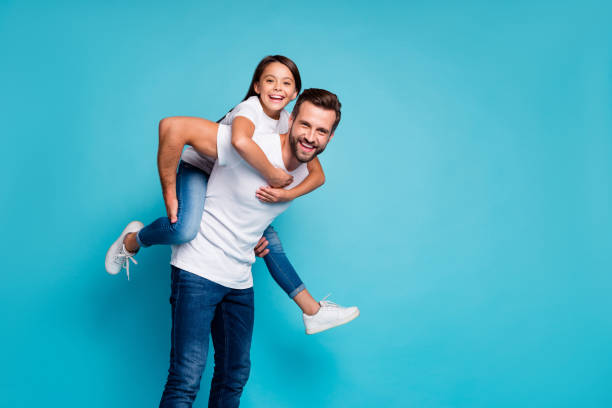 portrait of cheerful people laughing piggyback wearing white t-shirt denim jeans isolated over blue background - daddy stock pictures, royalty-free photos & images