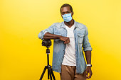 Portrait of cheerful photographer or video blogger with surgical medical mask smiling at camera with professional digital dslr camera on tripod. indoor studio shot isolated on yellow background