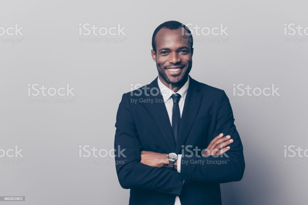 Portrait of cheerful, positive, attractive, rich manager in black suit with tie having his arms crossed looking at camera isolated on grey background stock photo
