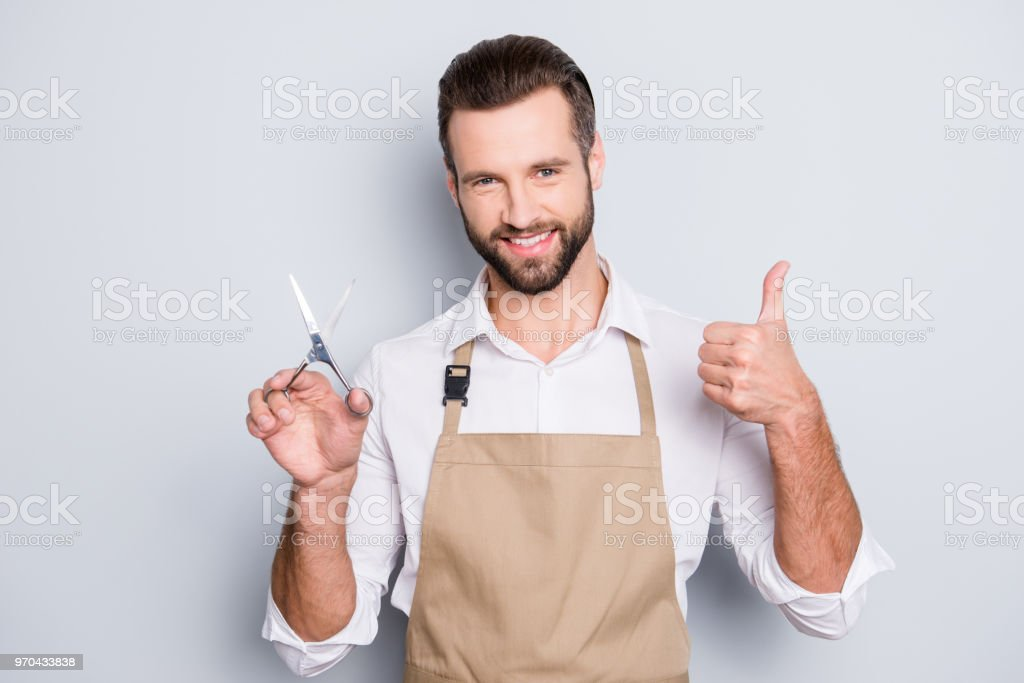 Portrait of cheerful positive barber with stubble in shirt having scissors in hand showing thumb up approve sign with finger, looking at camera, isolated on grey background - foto stock