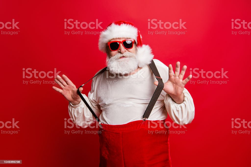 Portrait of cheerful positive dreamy funky Santa congratulations best wishes pulling suspenders ready to feast congrats isolated over bright vivid red background stock photo