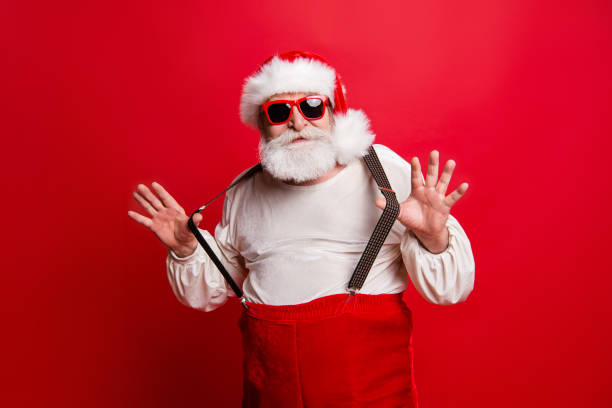 portrait of cheerful positive dreamy funky santa congratulations best wishes pulling suspenders ready to feast congrats isolated over bright vivid red background - funky stock pictures, royalty-free photos & images