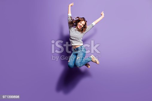 istock Portrait of cheerful positive girl jumping in the air with raised fists looking at camera isolated on violet background. Life people energy concept 971399898