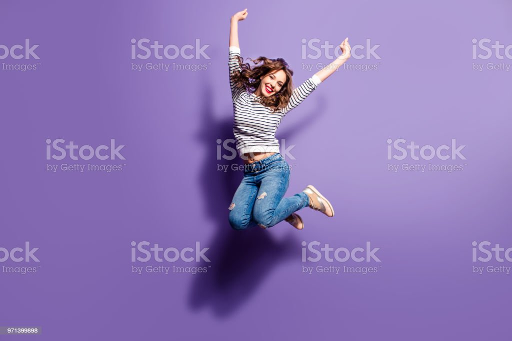 Portrait of cheerful positive girl jumping in the air with raised fists looking at camera isolated on violet background. Life people energy concept stock photo