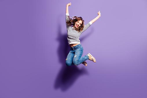 一個開朗積極的女孩的肖像跳在空中 舉起拳頭看著相機孤立的紫羅蘭背景生活人能量概念 照片檔及更多 一個人 照片