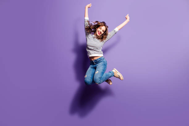 portrait of cheerful positive girl jumping in the air with raised fists looking at camera isolated on violet background. life people energy concept - donna foto e immagini stock