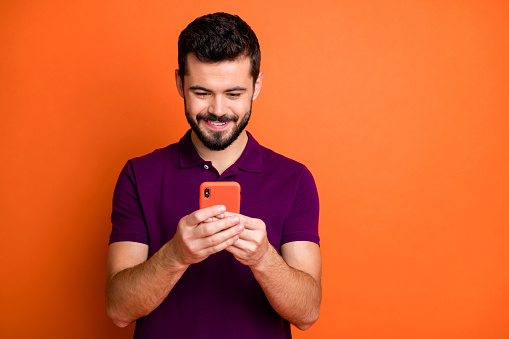 Portrait Of Cheerful Positive Guy Use His Cell Phone Chatting With Social Media Friends Comment Reposts Wear Modern Youth Outfit Isolated Over Vibrant Color Background Stock Photo - Download Image Now