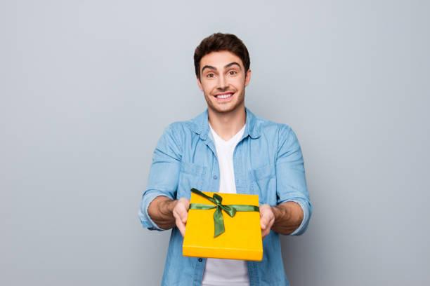 Portrait of cheerful positive smiling guy in jeans shirt giving box picture id931696418?b=1&k=6&m=931696418&s=612x612&w=0&h=i91dqwueh3kjyudm frpbodgkin987gikq7aqwkawzw=