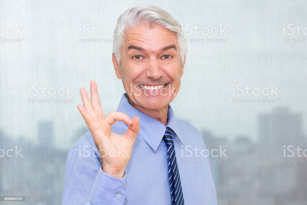 Portrait of cheerful senior businessman showing ok stock photo