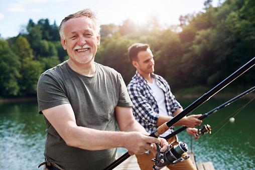 Portrait of cheerful senior man fishing