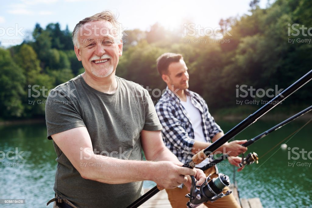 Portrait of cheerful senior man fishing stock photo
