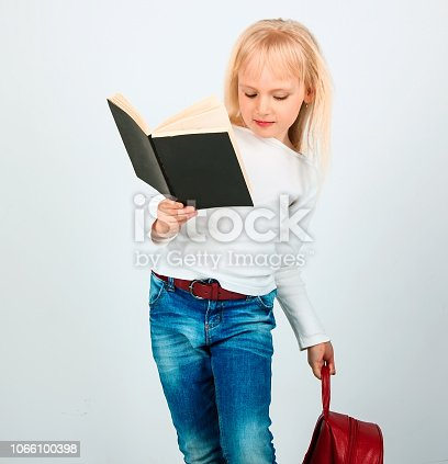 istock Portrait of cheerful smiling little schoolgirl girl with big book. 1066100398